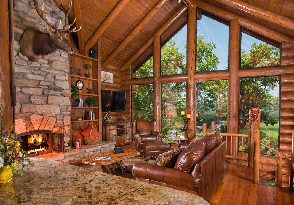 Main living area with large windows, leather furniture and fireplace at The Bluff House.